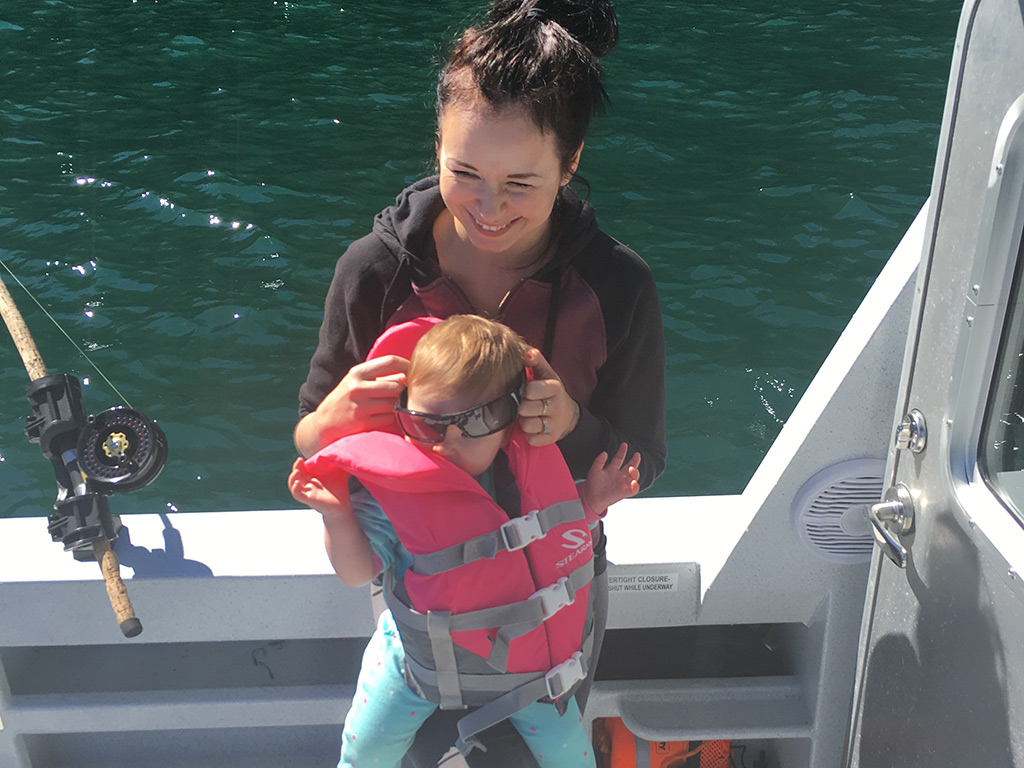 a smiling woman and her child wearing a life vest